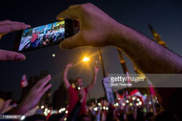 A man takes a video on his mobile phone as thousands of Lebanese protesters rally against sectarian government and call for the removal of the...