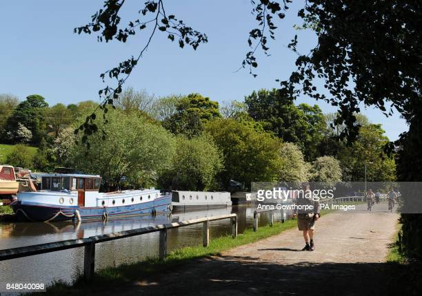A man takes a walk along the Leeds and Liverpool Canal at Five Rise Locks Bingley West Yorkshire as the warm weather continues across the UK