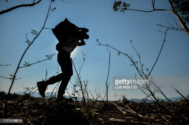 TOPSHOT A man takes an irregular road after crossing the Tachira river from San Antonio del Tachira in Venezuela to Cucuta in Colombia near the Simon...