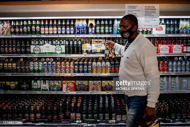 Man takes beers from a fridge inside a liquor shop at the Bara taxi rank in Soweto, Johannesburg, on June 1, 2020. - South Africa moved into level...