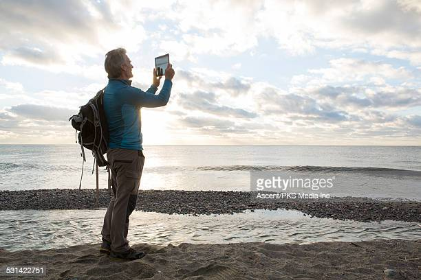 Man takes digital tablet picture from beach,to sea