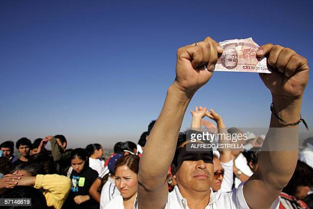 A man 'takes energy' with a Mexican Peso bill on the top of the Sun Pyramid in Teotihuacan Mexico during the spring equinox 21 March 2006 Since...