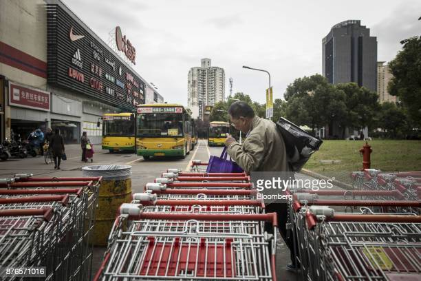 A man takes his purchases from a shopping cart outside an RTMart hypermarket operated by Sun Art Retail Group Ltd in Shanghai China on Monday Nov 20...