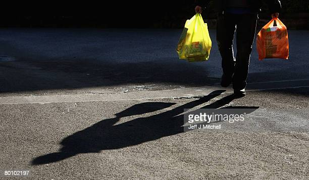 Man takes his shopping home in plastic carrier bags March 4, 2008 in Glasgow, Scotland. The Prime Minister Gordon Brown has stated that he will force...
