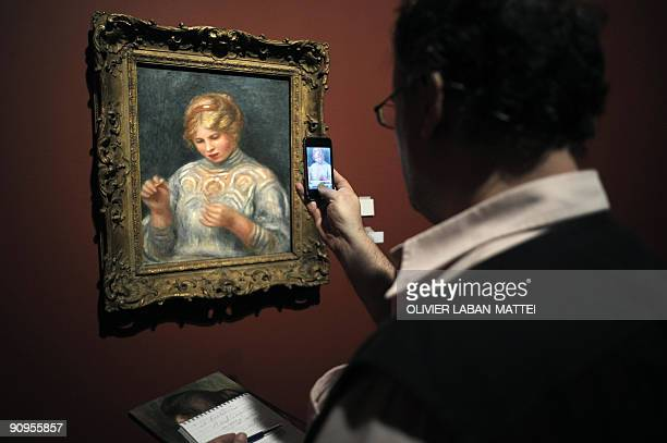 A man takes in picture with a telephone a painting La Frivolité by French artist Pierre Auguste Renoir during the exhibition Renoir au XXe siècle on...