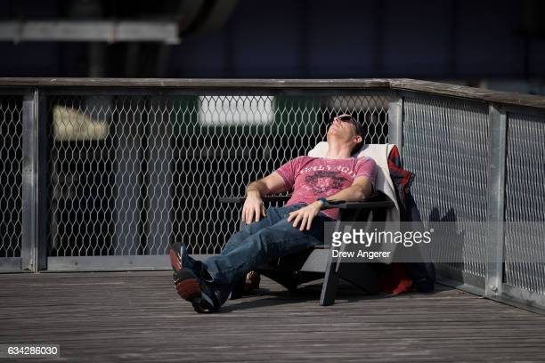 Man takes in the sun at the South Street Seaport during the lunch hour, February 8, 2017 in New York City. As temperatures touched 60 degrees on...