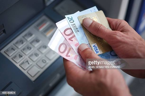 A man takes out Euro banknotes from an automated teller machine at a cash point of the French bank 'La Banque Postale' in Carquefou Western France on...