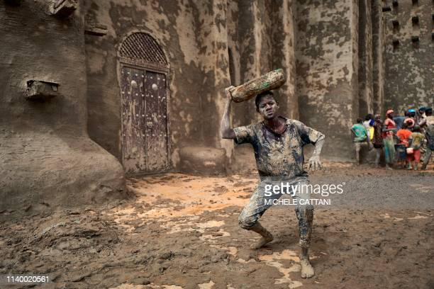 A man takes part in the annual rendering of the Great Mosque of Djenne in central Mali on April 28 2019 Several thousand residents of the historic...