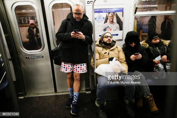 Man takes part in the No Pants Subway Ride braving freezing temperatures as others are seen covered for cold weather on January 7, 2018 in New York...