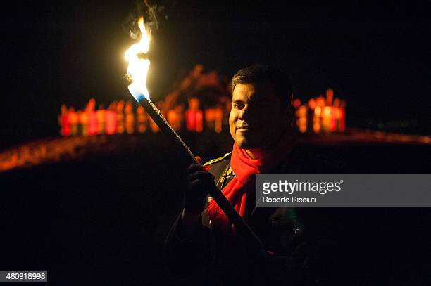 A man takes part in the torchlight procession as it makes its way through Edinburgh for the start of the Hogmanay celebrations on December 30 2014 in...