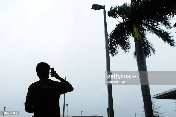 A man takes phone pictures as Hurricane Irma arrives into southwest Florida on September 10 2017 in Fort Myers Florida With businesses closed...