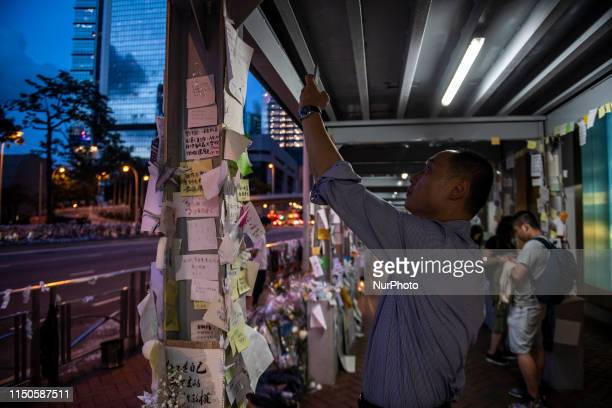 A Man takes photo of a memorial set up in Honor of a man who died after falling from a scaffolding in Pacific Place while protesting demanding the...