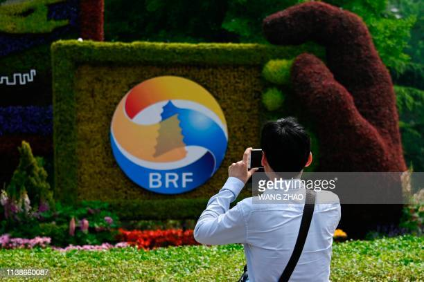 A man takes photo of a sign promoting the Belt and Road Forum in Beijing on April 22 2019