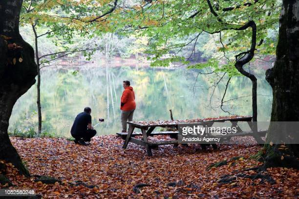 A man takes photo of a woman by the lake at Yedigoller National Park during autumn season in Bolu province of Turkey on October 19 2018 Forests cover...