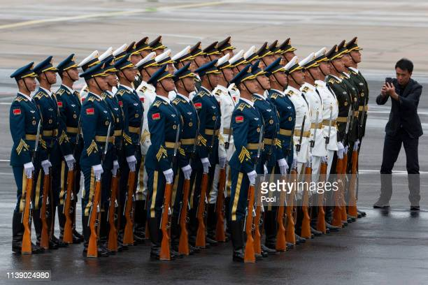 A man takes photo of Chinese honor guards awaiting the arrival of Myanmar's leader Aung San Suu Kyi by plane to the special plane terminal of the...