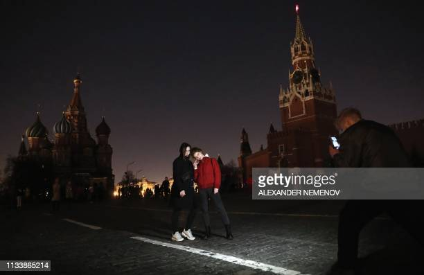 "Man takes photo of two women posing at the Red Square during the ""Earth Hour"" environmental campaign in central Moscow on March 30, 2019. - Millions..."