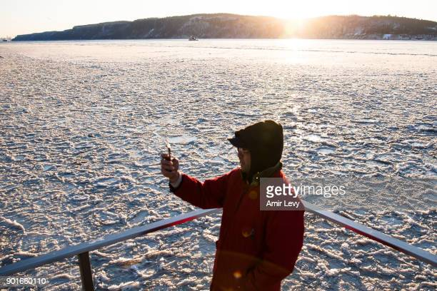 A man takes photo on a watrfront deck near the frozen Hudson River on January 5 2018 in Dobbs Ferry New YorkExtreme low tempratures and wind are...