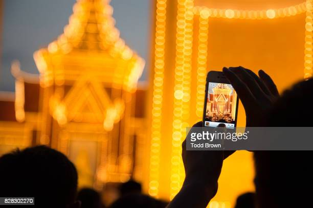 man takes photo with smart phone of king sihanouk's funeral - phnom penh stock pictures, royalty-free photos & images