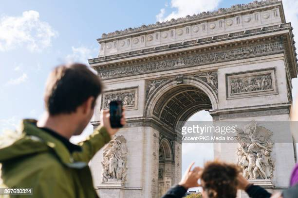 Man takes photo with smartphone of the Arc de Triomphe
