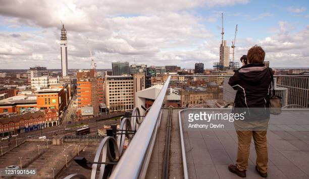 Man takes photograph from the roof of the Library of Birmingham in Birmingham city centre on March 20, 2020 in Birmingham, England.