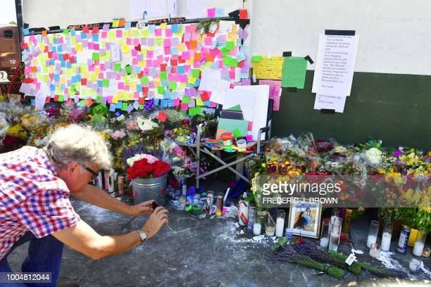 A man takes photographs at a memorial for Melyda Corado the assistant manager at the Silver Lake Trader Joe's who was killed in a July 21 shootout...