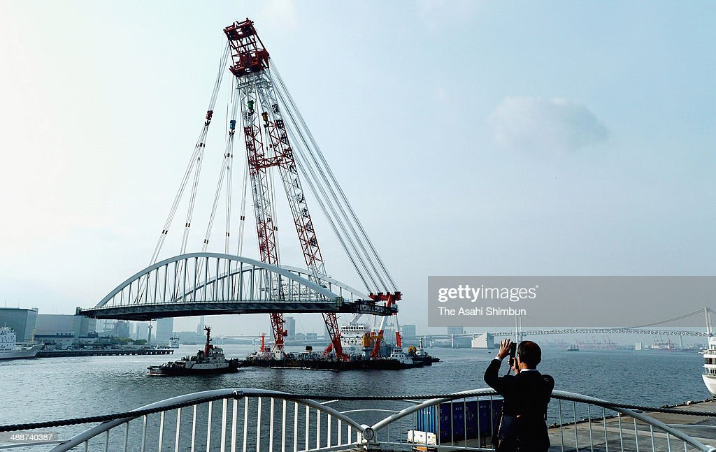A man takes photographs of a 2,600-ton new bridge carried by a huge crane on May 8, 2014 in Tokyo, Japan. The 120-meter bridge, assembled at Yokohama Port not to disturb the traffic of the Sumida River, will be part of Loop Line 2 which is an expected major traffic artery linking major venues at the 2020 Tokyo Summer Olympics.