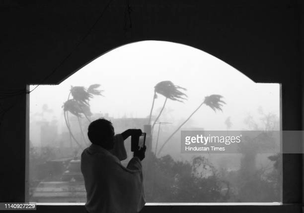 A man takes photos as cyclone Fani hits the coast on May 3 2019 in Puri India Cyclone Fani on Friday lashed Odisha triggering heavy rainfall...