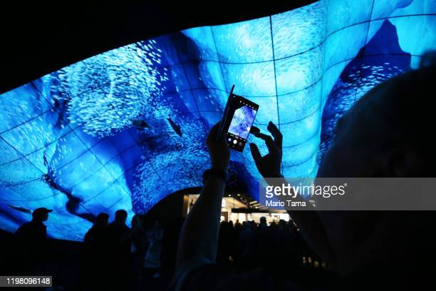Man takes photos beneath curved OLED screens at the LG Electronics booth during CES 2020 at the Las Vegas Convention Center on January 7, 2020 in Las...