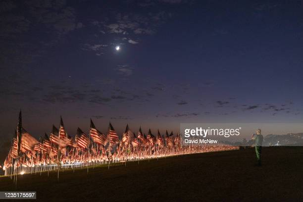 Man takes photos during the 14th annual Waves of Flags on the eve of the 20th anniversary of the September 11 terror attacks in Alumni Park at...