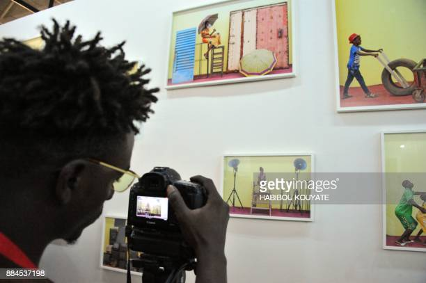 A man takes photos during the opening of the 11th Rencontres de Bamako' the African Biennale of Photography in Bamako on December 2 2017 / AFP PHOTO...