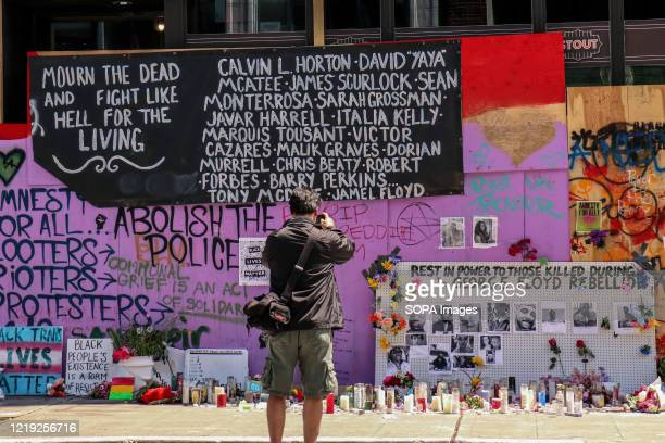 "Man takes photos of a makeshift memorial in the so-called ""Capitol Hill Autonomous Zone"" in Seattle. Protesters declared a Cop Free Zone near where..."