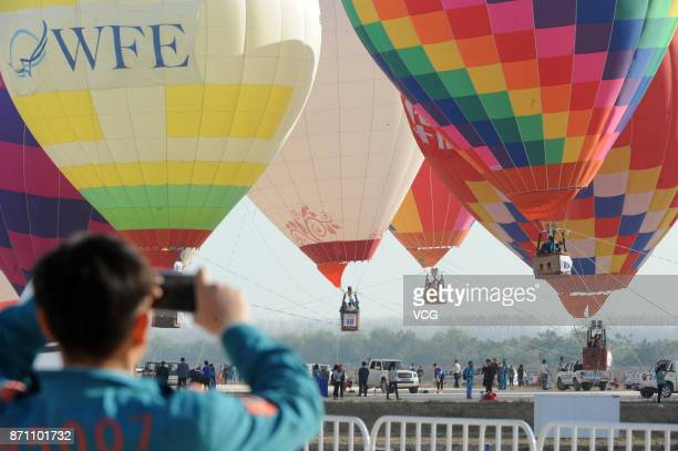 A man takes photos of couples holding their weddings in the hot air balloons during 2017 World Flyin Expo on November 6 2017 in Wuhan Hubei Province...