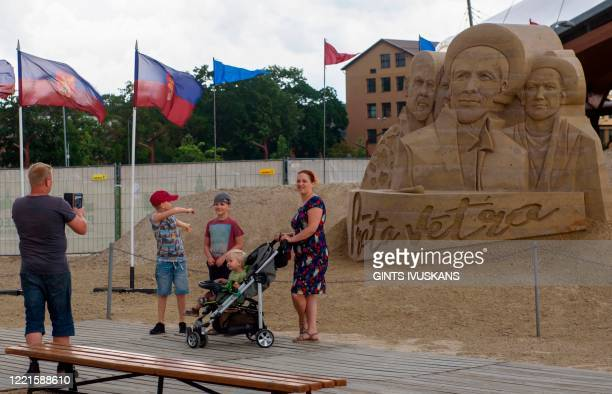 A man takes photos of his family in front of a sand sculptue titled Brainstorm at the Sand Sculpture Park in Jelgava Latvia on June 20 2020 The...