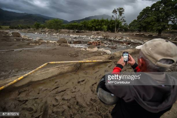 A man takes photos of La Paila river after a mudslide due to heavy rains affected Corinto in Cauca department southwest Colombia on November 8 2017...