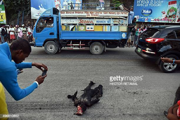A man takes photos of the burnt body of a man in the commune of Petion Ville in PortauPrince on November 12 2015 The man was burned alive with tires...