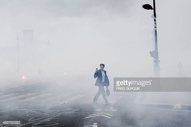 A man takes photos while walking in the flares' smoke during a demonstration staged by striking workers of the French staterun rail operator SNCF...