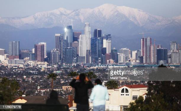 A man takes photos with snowcapped mountains standing behind the skyline of downtown of the city on February 11 2019 in Los Angeles California A...