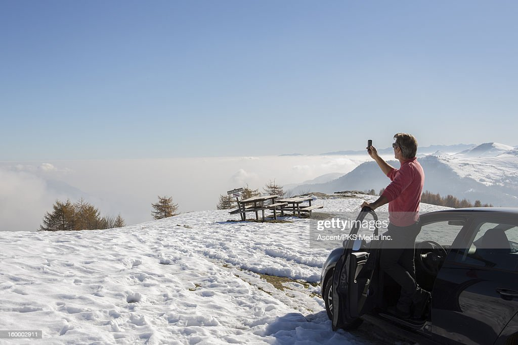 Man takes pic from car door, with cell phone : Stock Photo