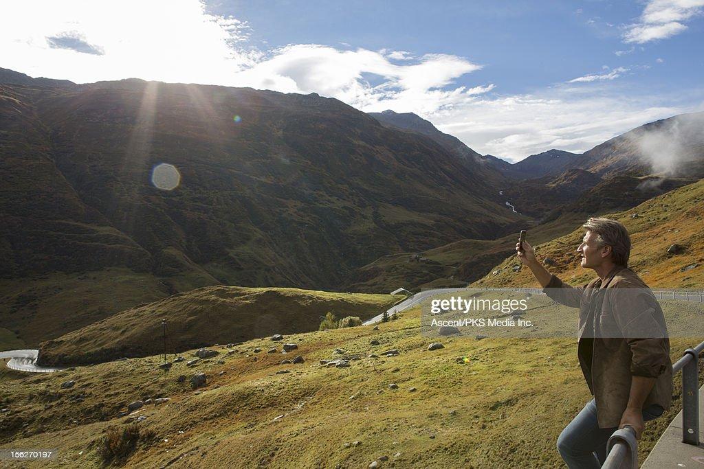 Man takes picture by roadside, near Furka Pass : Bildbanksbilder