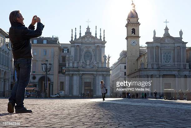 man takes picture of urban piazza, with cell phone - turin stock pictures, royalty-free photos & images