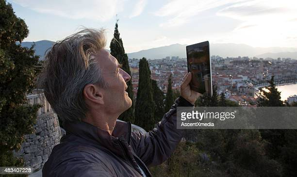 Man takes picture with digital tablet at city overlook