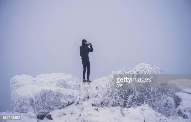Man takes pictures as he stands in the snowy landscape of the Brunhildisfelsen rock on the Grosser Feldberg mountain near Schmitten, western Germany,...