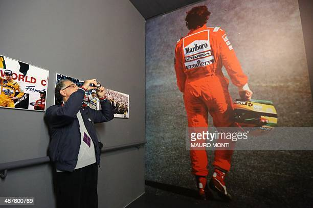 A man takes pictures as he visits an exhibition which pays tribute to Brazilian's F1 driver Ayrton Senna during a ceremony to commemorate the 20th...