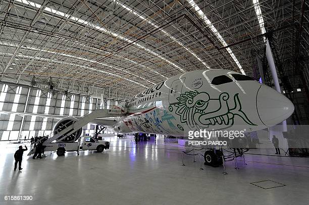 A man takes pictures during the presentation to the media of the new AeromExico's Boeing 7879 Dreamliner plane called 'Quetzalcoatl' in Mexico City...