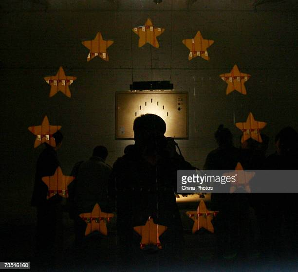 A man takes pictures in front of decorations featuring the European Union flag formed by lighters at the Lighter Mechanisms Exhibition in an art...
