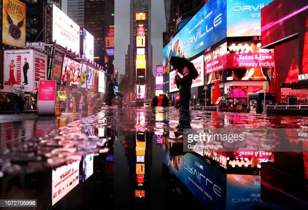 A man takes pictures in Times Square during a rain storm on November 26 2018 in New York City