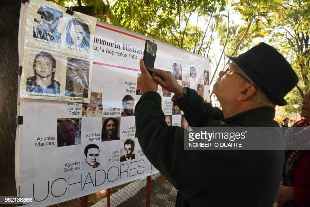 A man takes pictures of a banner depicting victims of Alfredo Stroessner's dictatorship during a ceremony in which the Paraguayan state offered an...