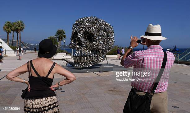 A man takes pictures of iron skull prior to the UEFA Champions League draw in Monaco on August 27 2014 The 32 clubs 22 of which qualified...