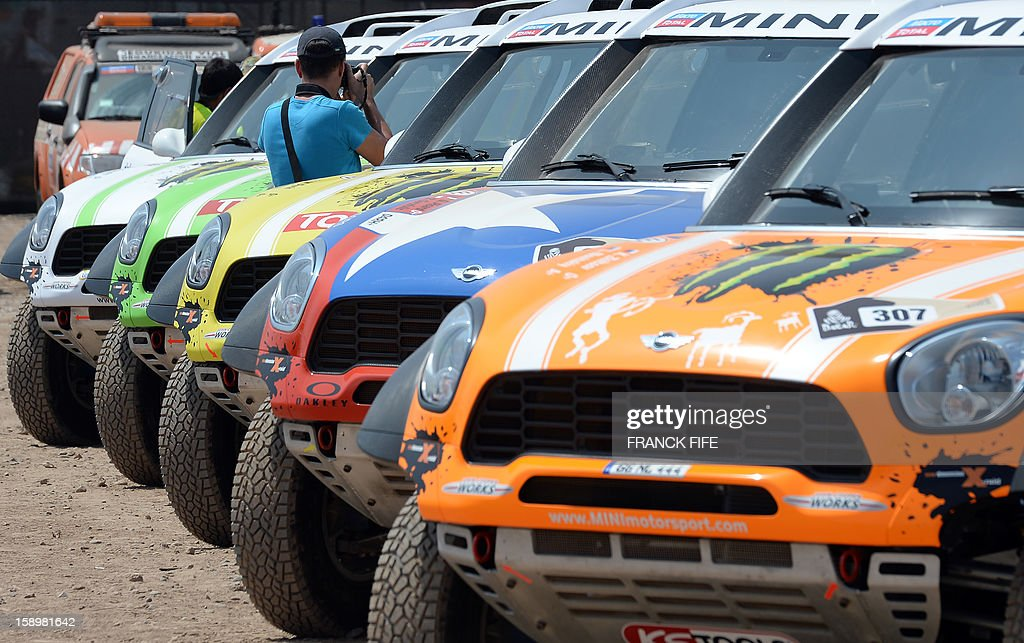 A man takes pictures of Minis in Lima on January 4, 2013, ahead of the 2013 Dakar Rally which this year will thunder through Peru, Argentina and Chile from January 5 to 20.