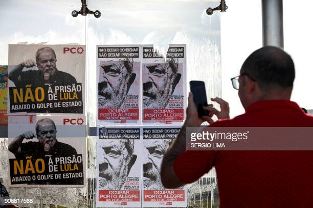 A man takes pictures of posters placed at a bus stop in Brasilia on January 22 2018 in support of Brazilian former President Luiz Inacio Lula de...